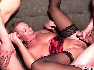 Matures Blonde Woman Is Wearing Satin Corset And Black Stockings While Having Orgy With Two Guys